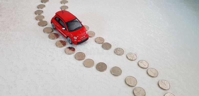 Κόκκινη εξουσιοδότηση 500 παιχνίδι abarth που κάνει τον τρόπο του στην οδική γραμμή φιαγμένη από νομίσματα ενός ισραηλινά Shekel στοκ εικόνα