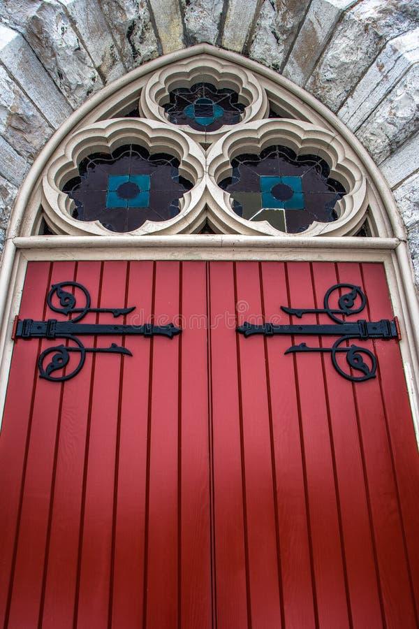 Κόκκινη ξύλινη πόρτα στη σχηματισμένη αψίδα είσοδο σε μια 19η εκκλησία αιώνα στοκ φωτογραφίες