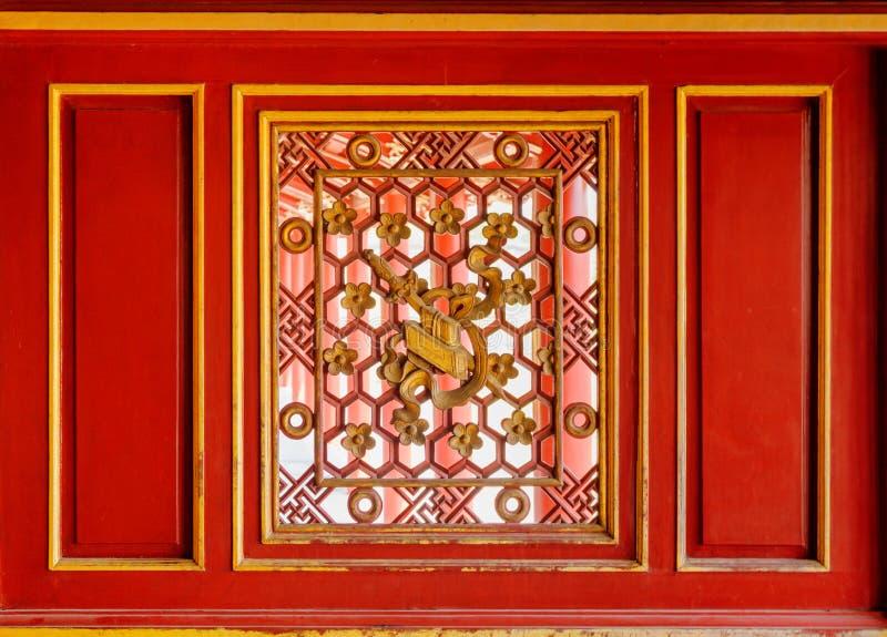 Κόκκινος ξύλινος τοίχος με το όμορφο χαρασμένο παράθυρο, η αυτοκρατορική πόλη στοκ εικόνα με δικαίωμα ελεύθερης χρήσης