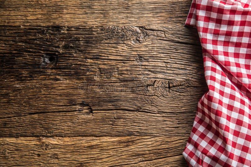 Κόκκινο ελεγμένο τραπεζομάντιλο κουζινών στον αγροτικό ξύλινο πίνακα στοκ εικόνες
