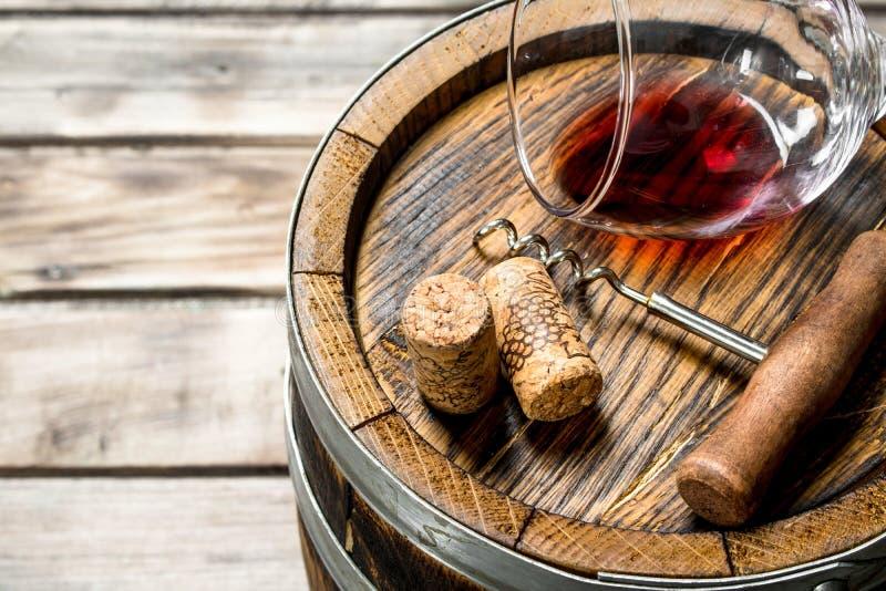 κόκκινο κρασί γυαλιού ανασκόπησης Ένα ποτήρι του κόκκινου κρασιού σε ένα παλαιό βαρέλι στοκ φωτογραφία