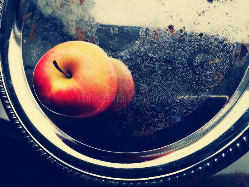 Κόκκινο μήλο σε έναν αρχαίο δίσκο μετάλλων στοκ εικόνα με δικαίωμα ελεύθερης χρήσης