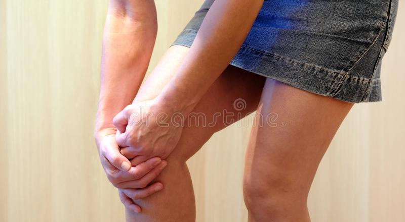 Κόκκινο υπόβαθρο περιοχής πόνου Το νέο κορίτσι άρπαξε το γόνατό της σε μια τακτοποίηση του πόνου Να πάσσει από την κοινή ασθένεια στοκ φωτογραφίες με δικαίωμα ελεύθερης χρήσης