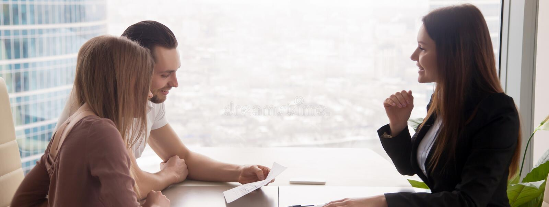 Κτηματομεσίτης που παρουσιάζει στο σχέδιο καινούργιων σπιτιών παντρεμένων ζευγαριών στοκ εικόνες