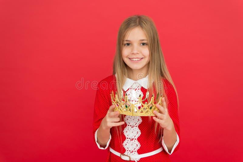 Κυρία λίγη πριγκήπισσα Χαριτωμένη κορώνα λαβής χαμόγελου κοριτσιών ενώ κόκκινο υπόβαθρο στάσεων Καλύτερο βραβείο για με Το παιδί  στοκ εικόνα με δικαίωμα ελεύθερης χρήσης