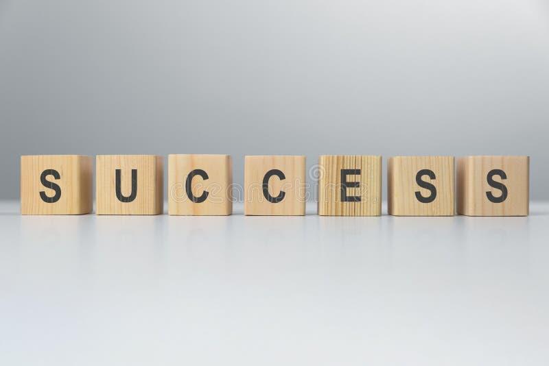 Λέξη επιτυχίας από τους ξύλινους φραγμούς στο γραφείο λευκό επιχειρησιακής απομονωμένο έννοια επιτυχίας στοκ φωτογραφία
