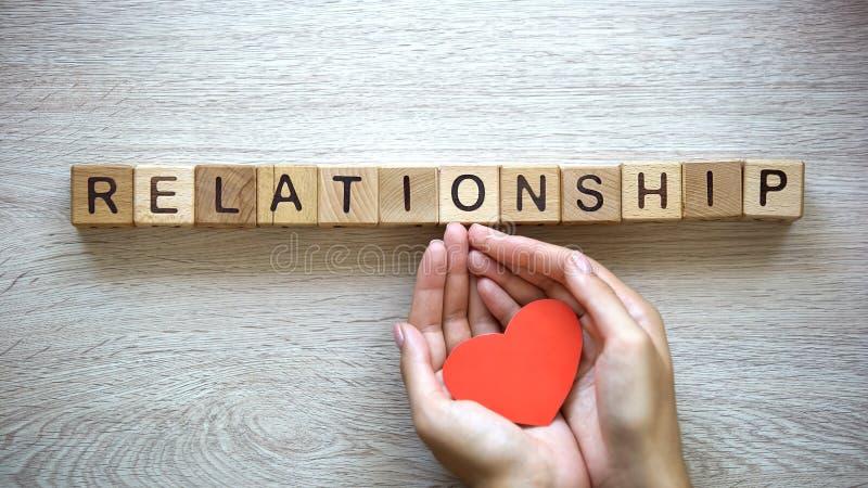 Λέξη σχέσης φιαγμένη από κύβους, θηλυκά χέρια που κρατούν την καρδιά εγγράφου, ερωτικός δεσμός στοκ εικόνες