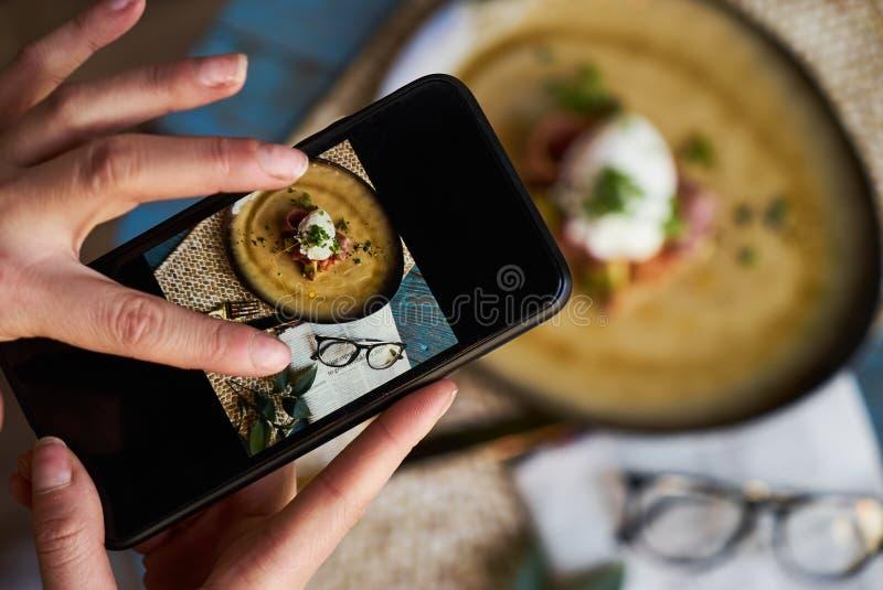 Λήψη της φωτογραφίας της φρυγανιάς με τα λαθραία αυγά, μπέϊκον, φασόλια στοκ εικόνα