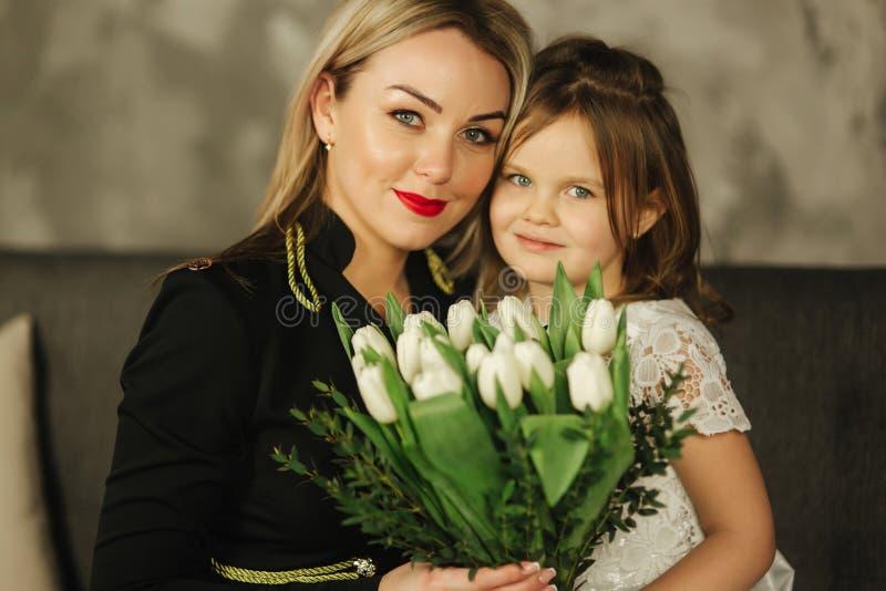 Λίγη κόρη δίνει στην ανθοδέσμη μητέρων των λουλουδιών Mom και κόρη στο σπίτι Ανθοδέσμη των λουλουδιών σε 8ο του Μαρτίου στοκ εικόνες με δικαίωμα ελεύθερης χρήσης