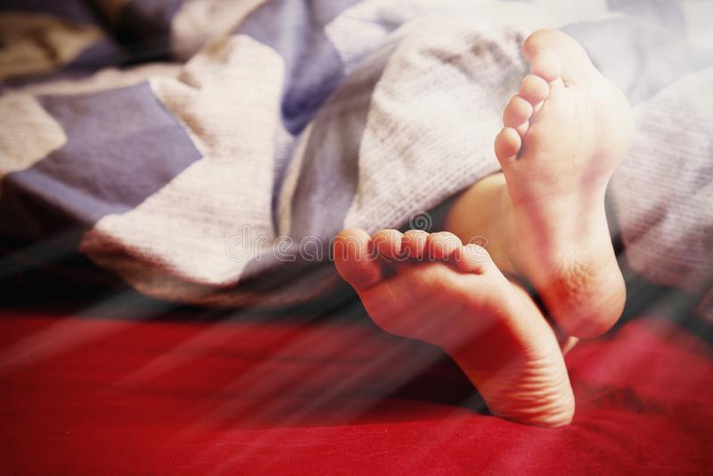 Λίγος ύπνος κοριτσιών παιδιών στο κρεβάτι στο σπίτι Πόδια κάτω από το κάλυμμα στο κρεβάτι της στην κρεβατοκάμαρα Έννοια καλημέρας στοκ εικόνα με δικαίωμα ελεύθερης χρήσης