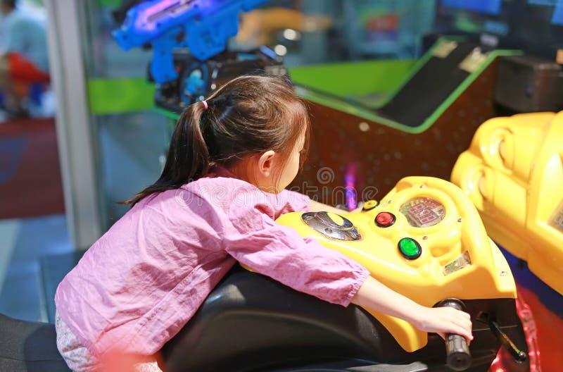 Λίγο ασιατικό παίζοντας arcade τηλεοπτικό παιχνίδι κοριτσιών παιδιών Αγώνας μοτοσικλετών στοκ εικόνα