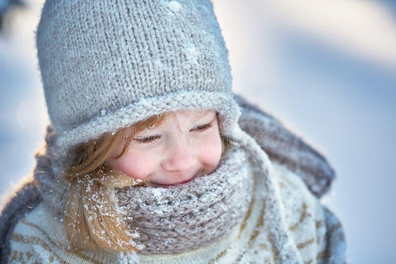 Λίγο εύθυμο κορίτσι σε ένα χιονισμένα καπέλο, ένα μαντίλι και ένα πουλόβερ Χιόνι γύρω στοκ εικόνες