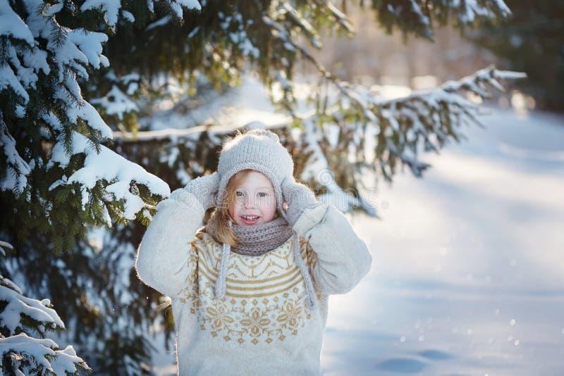 Λίγο εύθυμο κορίτσι στα χιονώδη ξύλα Ηλιόλουστη χειμερινή ημέρα στοκ φωτογραφία με δικαίωμα ελεύθερης χρήσης