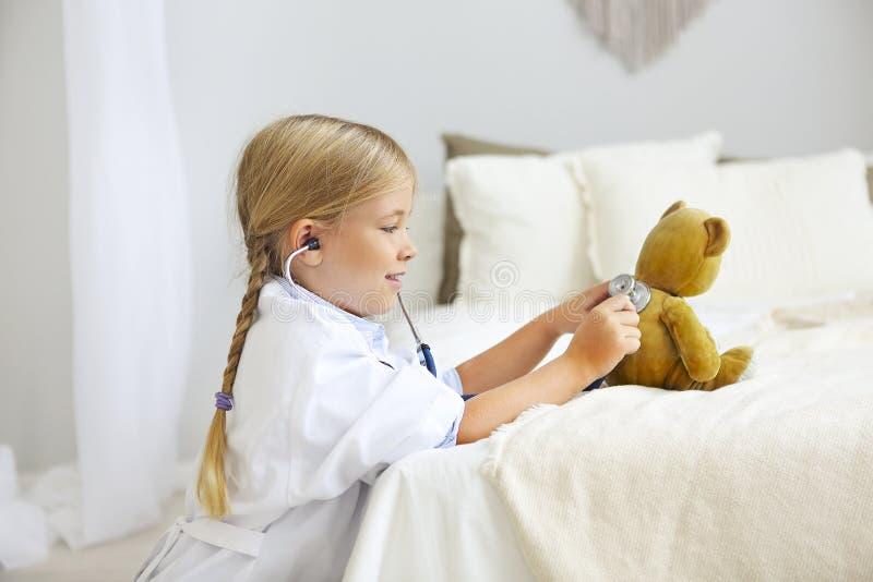 Λίγο ξανθό κορίτσι με το παιχνίδι στηθοσκοπίων με τη teddy αρκούδα στοκ εικόνες με δικαίωμα ελεύθερης χρήσης