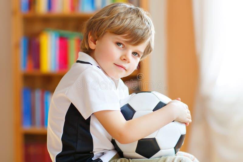 Λίγο ξανθό προσχολικό αγόρι παιδιών με το παιχνίδι φλυτζανιών ποδοσφαίρου ποδοσφαίρου προσοχής σφαιρών στη TV Αστείος ευτυχής φων στοκ φωτογραφία με δικαίωμα ελεύθερης χρήσης