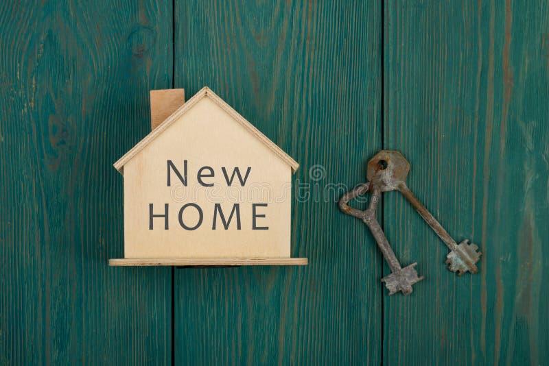 λίγο σπίτι με το κείμενο & x22 νέο home& x22  και κλειδί στο μπλε ξύλινο γραφείο στοκ φωτογραφία με δικαίωμα ελεύθερης χρήσης