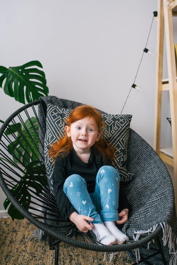 Λίγο χαριτωμένο redhead κορίτσι στα τζιν κάθεται στην πολυθρόνα Έκπληκτες συγκινήσεις στοκ εικόνα