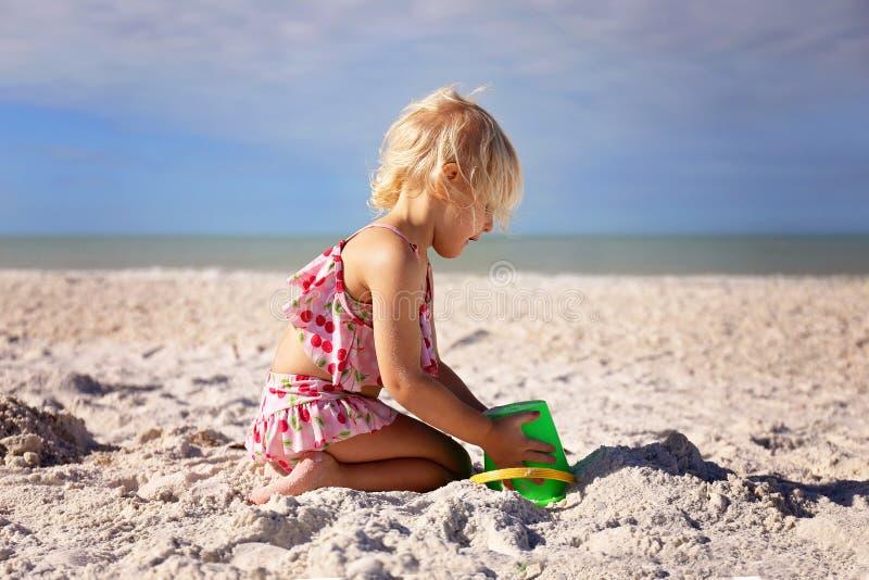 Λίγο παιδί μικρών παιδιών που παίζει στην παραλία που χτίζει μια άμμο Castle στοκ φωτογραφία