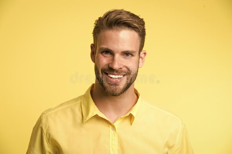 λαμπρό χαμόγελο Πρόσωπο χαμόγελου ατόμων που θέτει με βεβαιότητα το κίτρινο υπόβαθρο Ο σύμβουλος καταστημάτων ατόμων φαίνεται εύθ στοκ φωτογραφία με δικαίωμα ελεύθερης χρήσης
