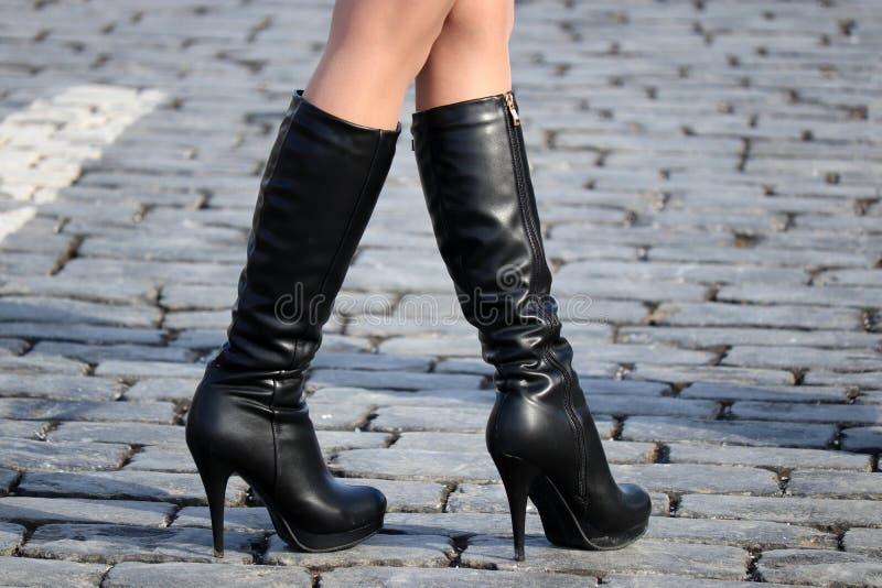 Λεπτά θηλυκά πόδια στις υψηλές μαύρες μπότες δέρματος με τα υψηλά τακούνια στοκ εικόνες