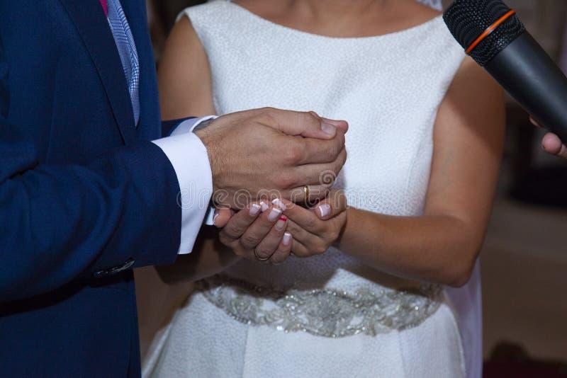 Λεπτομέρεια των χεριών της νύφης και του νεόνυμφου ακριβώς αυτή τη στιγμή στα οποία η νύφη δίνει τα arras στοκ εικόνα με δικαίωμα ελεύθερης χρήσης