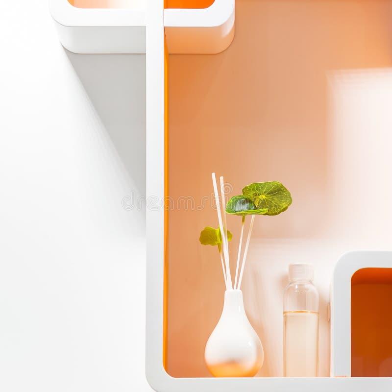 Λεπτομέρειες και στοιχεία του εγχώριου ντεκόρ και του εσωτερικού σχεδίου Καθαρίστε, διατάξτε Γεωμετρικά ράφια του άσπρου πορτοκαλ στοκ εικόνες