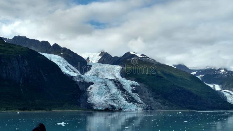 Λεπτός παγετώνας μεταξύ δύο βουνών που γλιστρούν αργά στο Ειρηνικό Ωκεανό με ένα νεφελώδες σκηνικό στοκ εικόνα