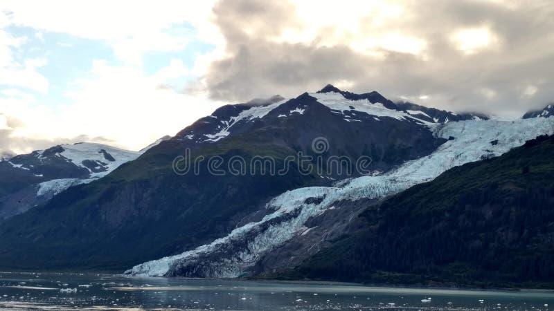 Λεπτός παγετώνας μεταξύ δύο βουνών που γλιστρούν αργά στο Ειρηνικό Ωκεανό με ένα νεφελώδες σκηνικό στοκ εικόνες με δικαίωμα ελεύθερης χρήσης
