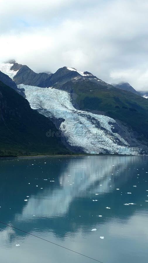 Λεπτός παγετώνας μεταξύ δύο βουνών που γλιστρούν αργά στο Ειρηνικό Ωκεανό με ένα νεφελώδες σκηνικό στοκ φωτογραφίες με δικαίωμα ελεύθερης χρήσης