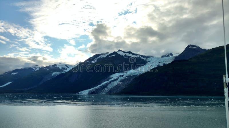 Λεπτός παγετώνας μεταξύ δύο βουνών που γλιστρούν αργά στο Ειρηνικό Ωκεανό με ένα νεφελώδες σκηνικό στοκ φωτογραφία