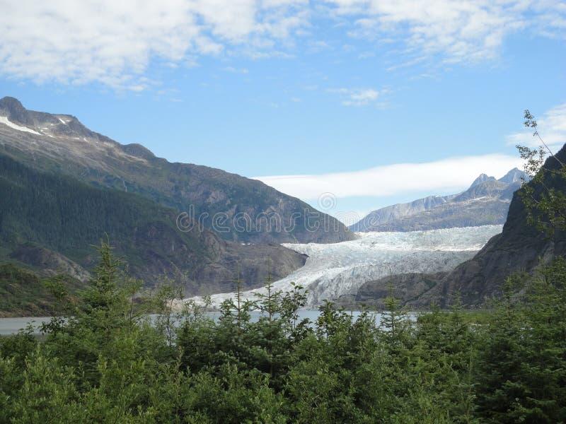 Λεπτός παγετώνας μεταξύ δύο βουνών που γλιστρούν αργά στο Ειρηνικό Ωκεανό με ένα νεφελώδες σκηνικό στοκ εικόνες