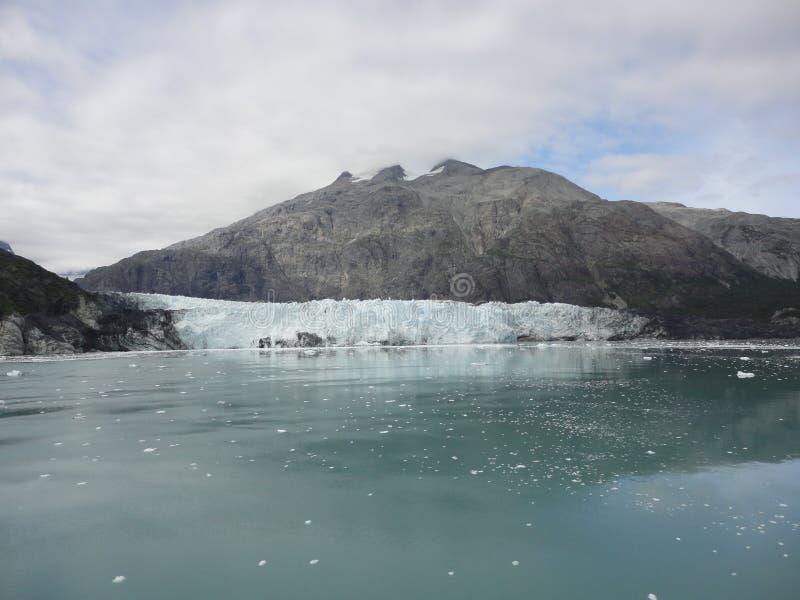 Λεπτός παγετώνας μεταξύ δύο βουνών που γλιστρούν αργά στο Ειρηνικό Ωκεανό με ένα νεφελώδες σκηνικό στοκ εικόνα με δικαίωμα ελεύθερης χρήσης