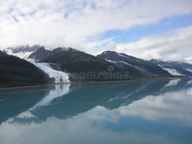 Λεπτός παγετώνας μεταξύ δύο βουνών που γλιστρούν αργά στο Ειρηνικό Ωκεανό με ένα νεφελώδες σκηνικό στοκ φωτογραφία με δικαίωμα ελεύθερης χρήσης