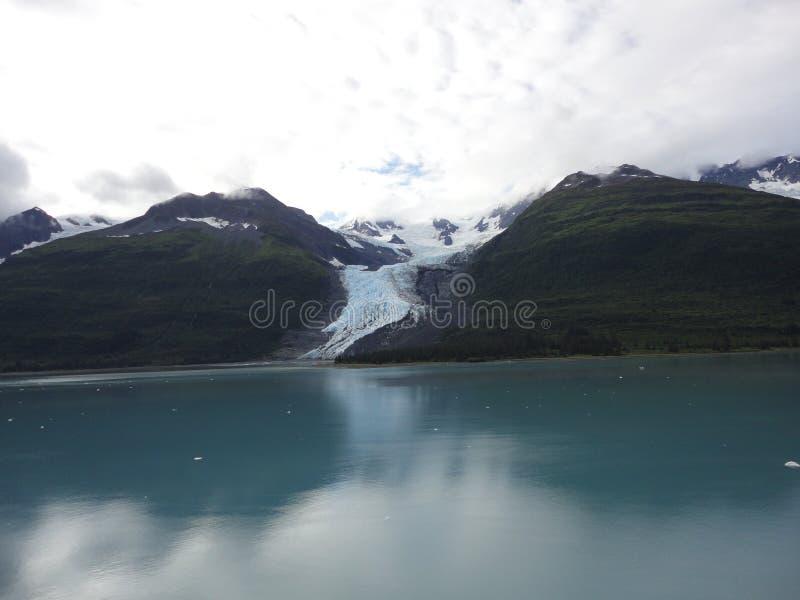 Λεπτός παγετώνας μεταξύ δύο βουνών που γλιστρούν αργά στο Ειρηνικό Ωκεανό με ένα νεφελώδες σκηνικό στοκ φωτογραφίες