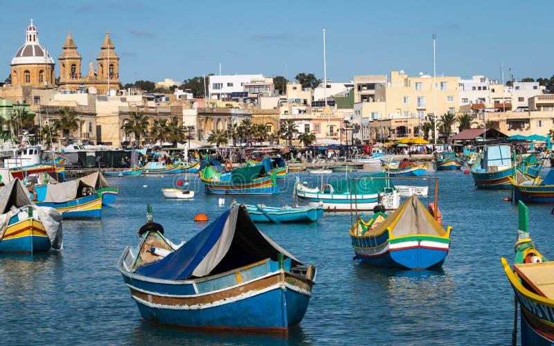 Λιμάνι Marsaxlokk με τις παραδοσιακές, ζωηρόχρωμες βάρκες Luzzu στον κόλπο με την αγορά στο υπόβαθρο στοκ εικόνες με δικαίωμα ελεύθερης χρήσης