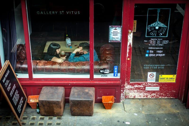 Λονδίνο, Ηνωμένο Βασίλειο - 5 Απριλίου 2015 Kingsland Rd Ζεύγος που κουβεντιάζει πέρα από μια μπύρα σε έναν καναπέ του Τσέστερφιλ στοκ φωτογραφία με δικαίωμα ελεύθερης χρήσης