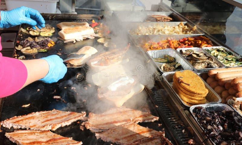 μάγειρες με τα μπλε γάντια μαγειρεύοντας τα λουκάνικα και τα σάντουιτς επάνω στοκ εικόνα με δικαίωμα ελεύθερης χρήσης