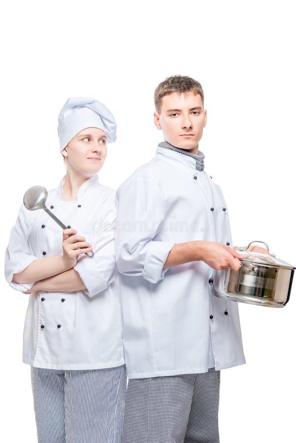 μάγειρες στα κοστούμια με ένα τηγάνι και μια τοποθέτηση κουταλών σε ένα λευκό στοκ φωτογραφίες