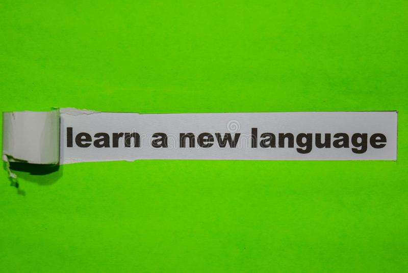 Μάθετε μια νέα έννοια γλώσσας, έμπνευσης και επιχειρήσεων σε πράσινο σχισμένο χαρτί στοκ φωτογραφίες