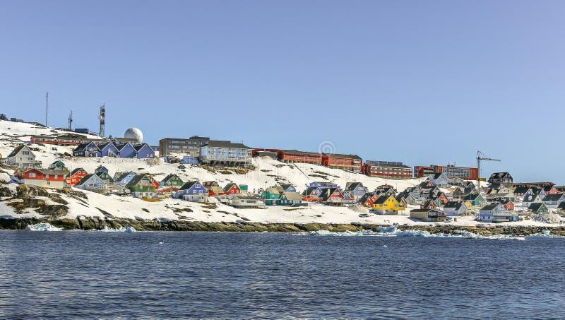 Μέρη των καλυβών Inuit και των ζωηρόχρωμων σπιτιών που τοποθετούνται στη δύσκολη ακτή κατά μήκος του φιορδ, πόλη του Νουούκ, Γροι στοκ εικόνα με δικαίωμα ελεύθερης χρήσης