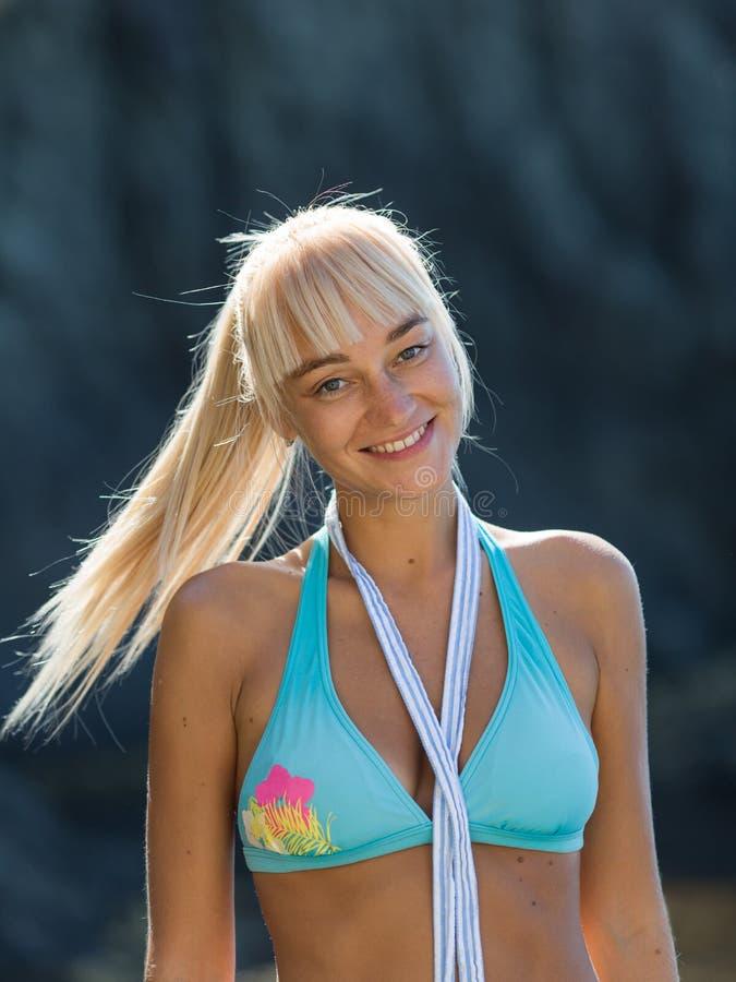 Μέση επάνω στο πορτρέτο του ελκυστικού θηλυκού προσώπου στο μπλε μαγιό στην παραλία στοκ εικόνα με δικαίωμα ελεύθερης χρήσης