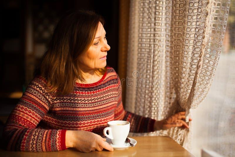 Μέση ηλικίας κυρία στο ριγωτό πουλόβερ που κοιτάζει σε όλο το παράθυρο με ένα φλιτζάνι του καφέ στοκ εικόνες με δικαίωμα ελεύθερης χρήσης