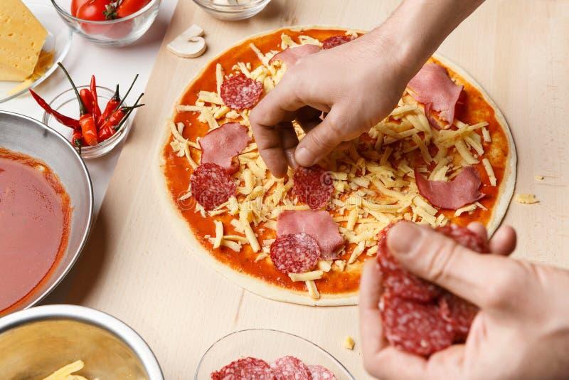 Μαγειρεύοντας πίτσα σαλαμιού αρχιμαγείρων, που προσθέτει τα συστατικά σε το στοκ φωτογραφία