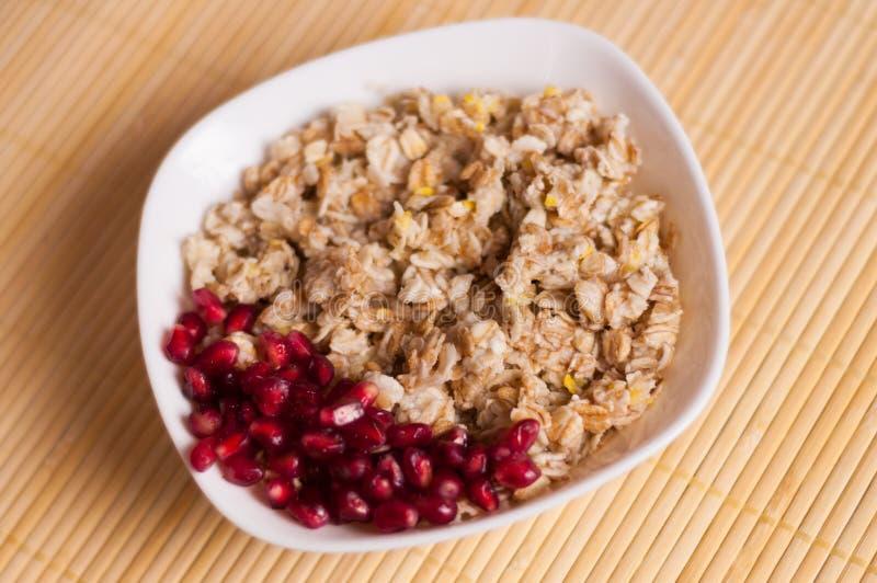 Μαγειρευμένοι yummy θερμοί oatmeal και σωρός των ώριμων φρέσκων σπόρων ροδιών στο άσπρο κεραμικό κύπελλο στοκ φωτογραφίες με δικαίωμα ελεύθερης χρήσης