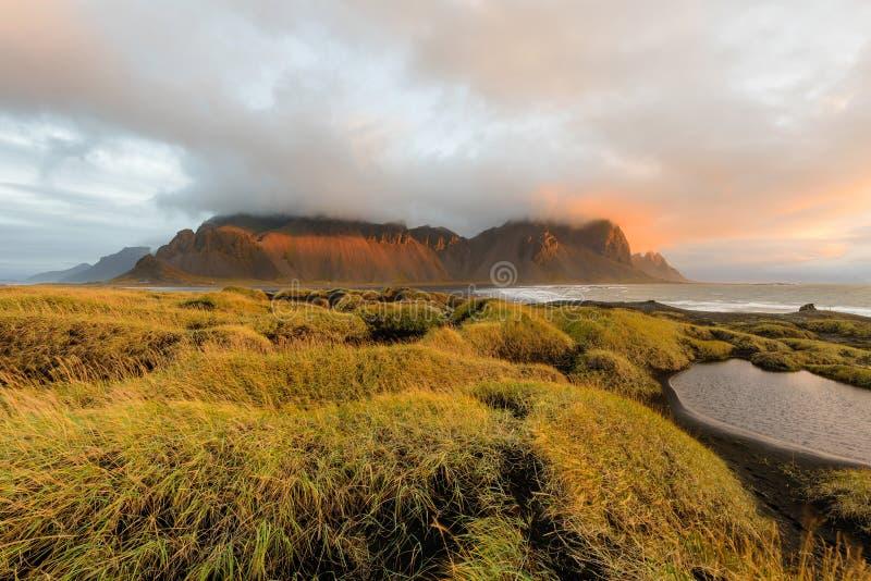 Μαγικό τοπίο των βουνών Vestrahorn και των μαύρων αμμόλοφων άμμου στην Ισλανδία στην ανατολή Πανοραμική άποψη του ακρωτηρίου Stok στοκ εικόνες