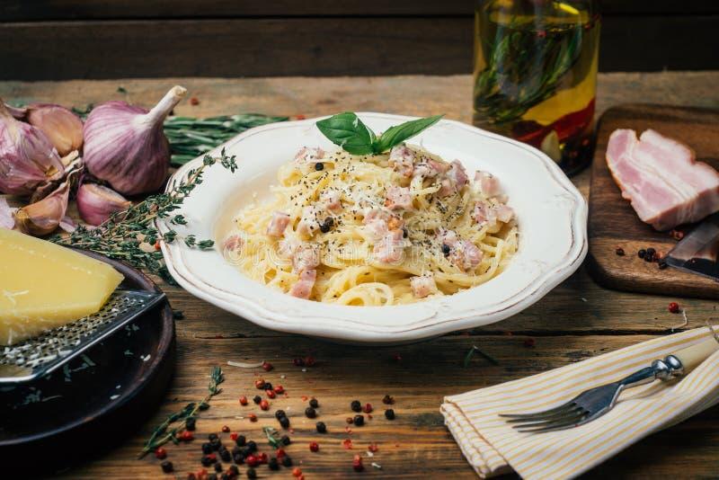 Μακαρόνια Carbonara Carbonara alla ζυμαρικών με μια σάλτσα, ένα μπέϊκον και ένα πιπέρι κρέμας σε ένα άσπρο πιάτο στοκ εικόνες
