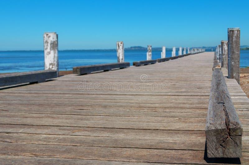 Μακρύς ξύλινος λιμενοβραχίονας, αποβάθρα με τον μπλε ωκεάνιο και σαφή ουρανό στοκ εικόνες με δικαίωμα ελεύθερης χρήσης