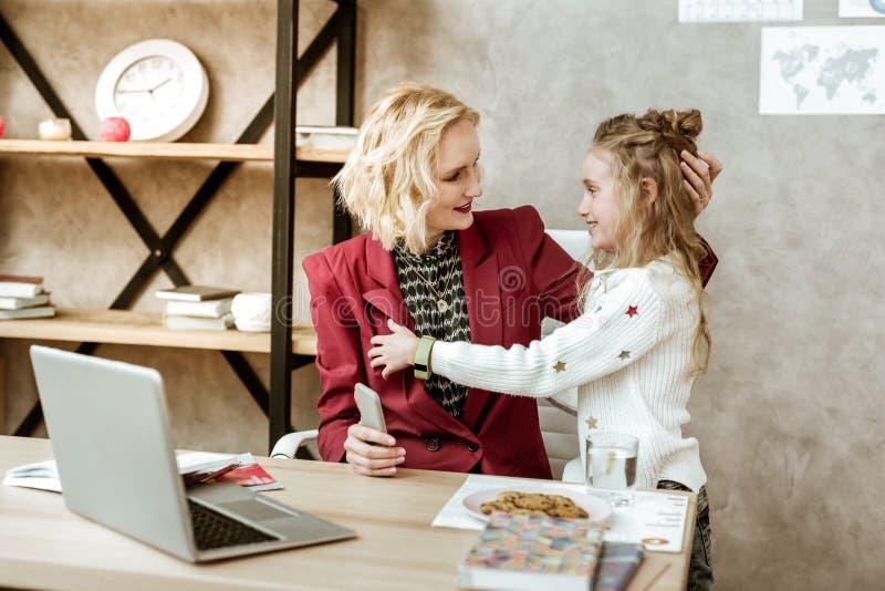 Μακρυμάλλη εύθυμα φέρνοντας μπισκότα μικρών κοριτσιών στην πολυάσχολη μητέρα της στοκ εικόνα