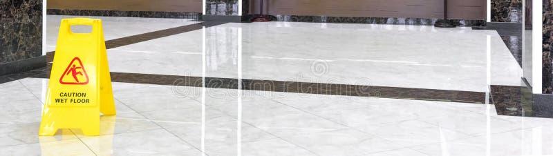 Μαρμάρινο λαμπρό πάτωμα σε έναν διάδρομο πολυτέλειας της επιχείρησης ή του ξενοδοχείου κατά τη διάρκεια του καθαρισμού στοκ εικόνα