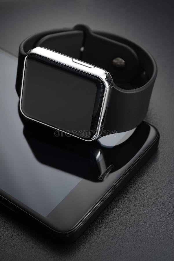 Μαύρα έξυπνα wristwatches και smartphone στοκ φωτογραφία με δικαίωμα ελεύθερης χρήσης